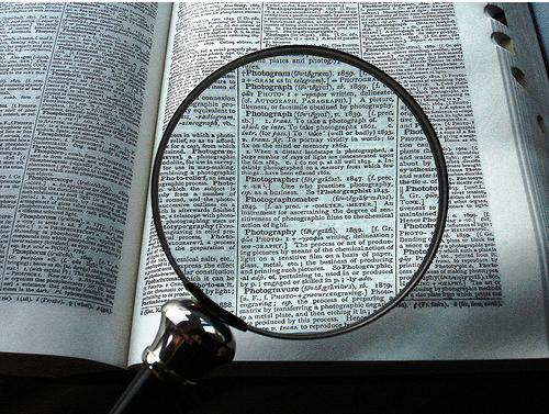 "A magnifying glass rests over a portion of the dictionary, enlarging the word ""photograph"" and its definition."