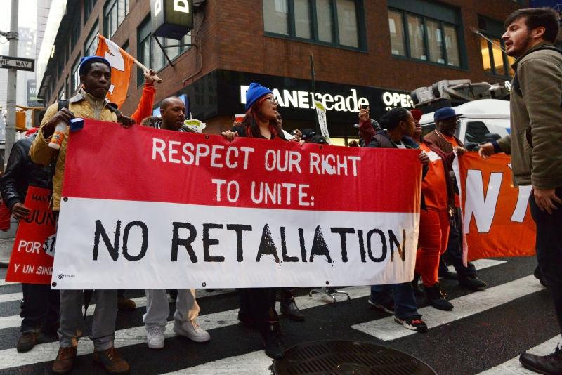 "Protesters carry a bright red and white banner reading ""No Retaliation"" through the streets."