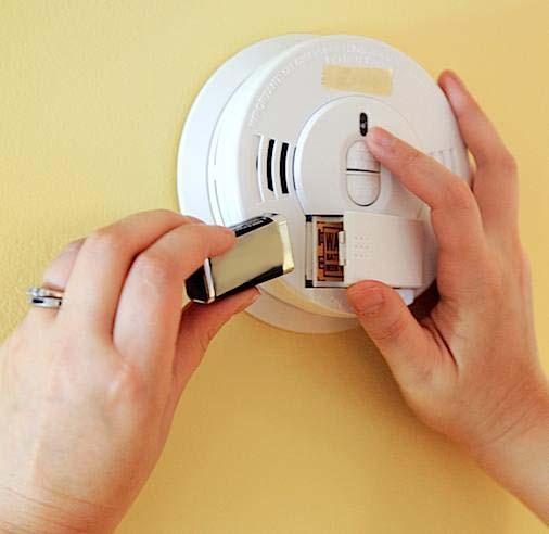 Hands grasp a white smoke detector mounted on a pale yellow wall as a new battery is inserted into the alarm.