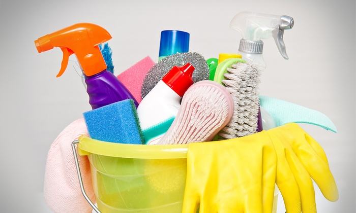 A yellow plastic bucket is full of vibrantly colored cleaning supplies, including brushes, sponges, and spray bottles.