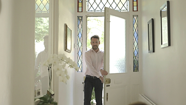 A nicely dressed man enters the front door of a home as light shines in the stained glass windows lining the door.