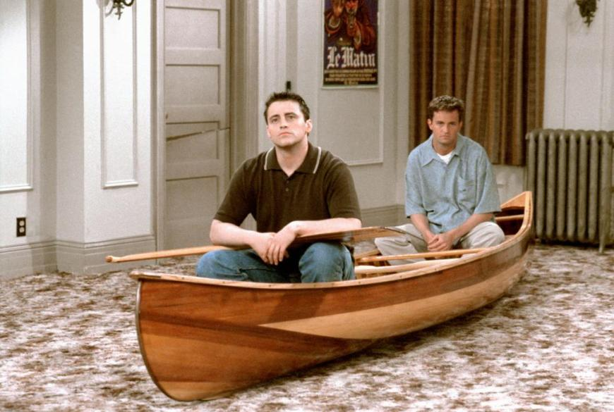 "Characters Joey and Chandler from the TV show ""Friends"" sit thoughtfully in a wooden canoe in the middle of their empty apartment."