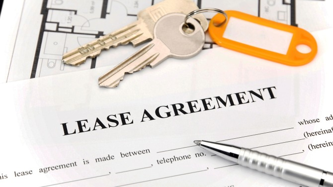 A silver pen and a set of keys are laying on top of a lease agreement.