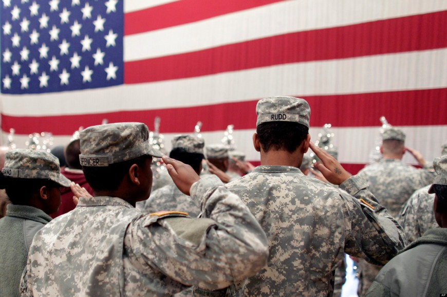 Soldiers dressed in camouflage stand at attention, saluting the large American flag stretched out before them.