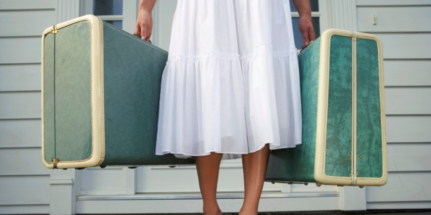 Only the lower half of a woman is shown as she stands on the porch in a white skirt with two teal suitcases in hand.