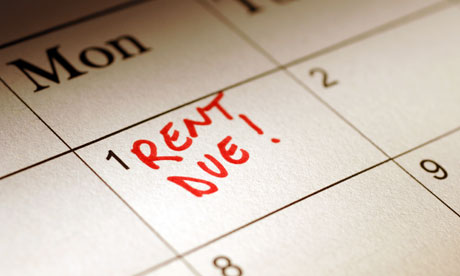 The first of the month on a desk calendar is marked in red marker as a reminder to pay the rent.